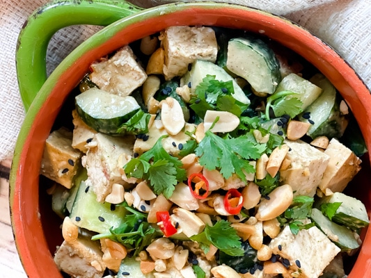 A green bowl filled with a vibrant spicy Asian tofu salad with cucumbers, cilantro, and peanuts.