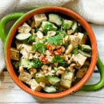 A green bowl filled with a vibrant spicy tofu salad with cucumbers, cilantro and peanuts.
