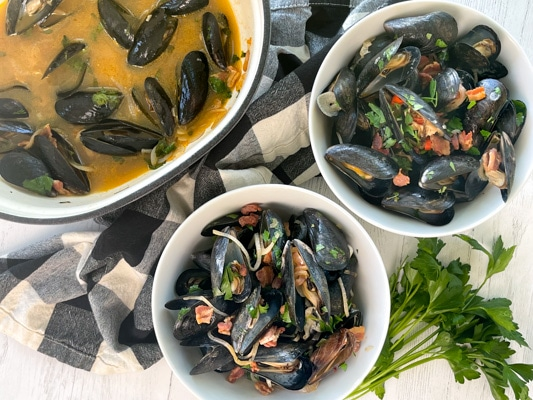 Two white bowls filled with steamed mussels and crusty bread on a white board, with a pot of mussels and green herbs on the side.