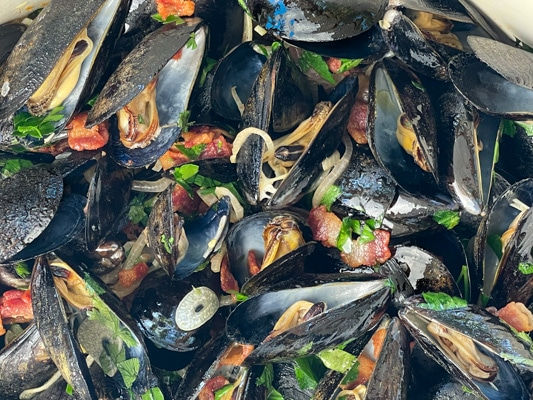 Close up shot of steamed mussels tossed with pieces of smoky bacon, sliced shallots, slices of garlic, and fresh green herbs.