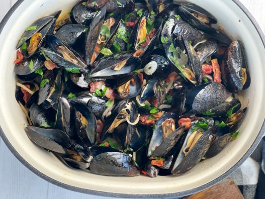 A large pot of steamed mussels tossed with pieces of smoky bacon, sliced shallots, slices of garlic, and fresh green herbs.