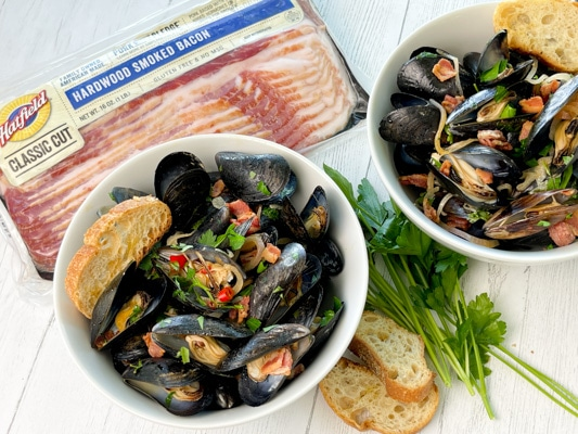 Two white bowls filled with steamed mussels and crusty bread on the side on a white board, with a package of Hatfield Smoked Bacon and herbs and bread on the side.
