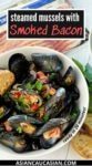 A white bowl filled with steamed mussels on a white board, with a pot of mussels and green herbs on the side.