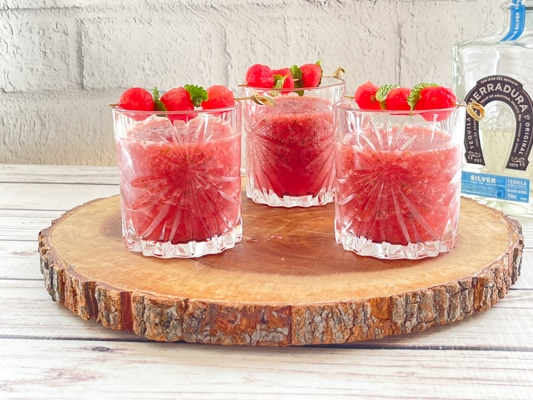 Three crystal glasses filled with boozy watermelon strawberry slushies on top of a rustic wooden tray with a bottle of tequila in the background.