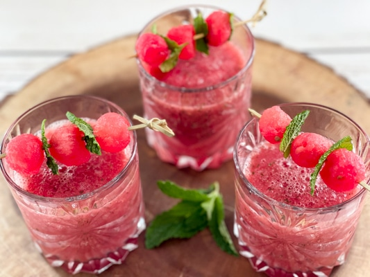Three crystal glasses filled with boozy watermelon strawberry slushies topped with melon balls, on top of a rustic wooden tray.