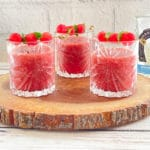 Three crystal glasses filled with watermelon strawberry slushies topped with melon balls, on top of a rustic wooden tray.