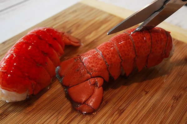 A pair of scissors cutting through the top side of a cooked lobster tail on top of a wooden cutting board.