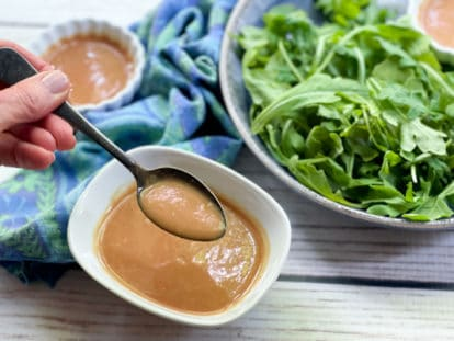 A woman's hand holding a spoon over a white bowl of homemade miso dressing with a bowl of greens and a blue napkin in the background on a white board.