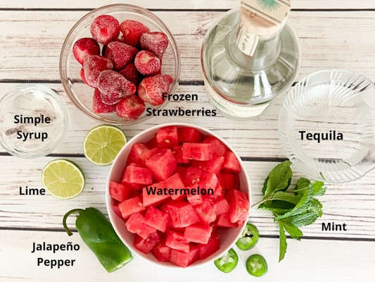 Ingredients on a white board for making boozy watermelon strawberry slushies: frozen strawberries, tequila, watermelon cubes, simply syrup, fresh mint, limes, and a jalapeño pepper.