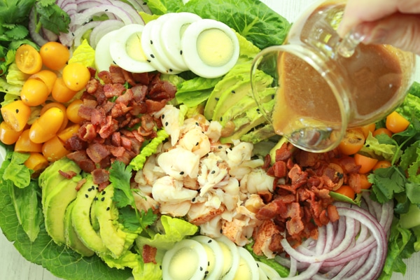A person pouring miso dressing on top of a vibrant lobster cobb salad with lots of greens.