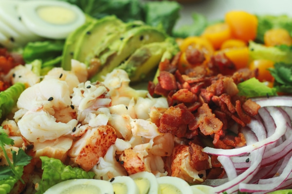 A close-up shot of vibrant lobster cobb salad on top of romaine greens.