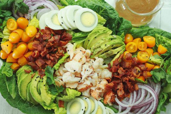 A platter of vibrant lobster cobb salad on top of romaine greens and a clear jar of miso dressing on the side.