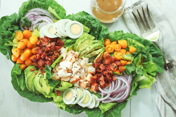 A platter of vibrant lobster cobb salad on top of romaine greens and a large fork and clear jar of miso dressing on the side.