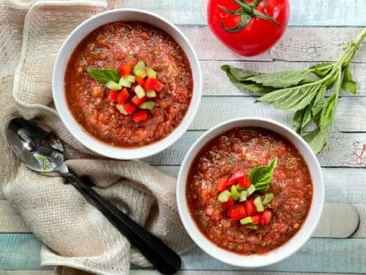 Two white bowls filled with spicy watermelon gazpacho on a wooden board, with ingredients on the side: a tomato, basil, and a spoon.