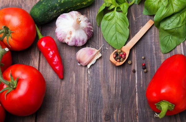 Tomatoes, pepper, basil, cucumber, and garlic on wooden table, ingredients for gazpacho