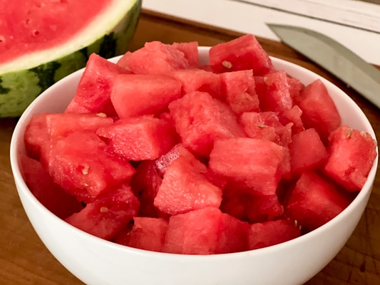 A white bowl filled with fresh watermelon cubes, with a watermelon half in the background.