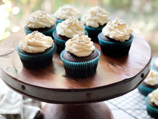 A close-up image of a chocolate miso cupcake with white frosting topped with silver sprinkles, on a wooden board.