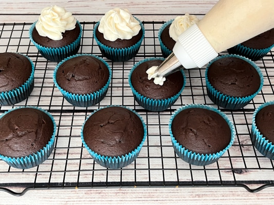 Chocolate miso cupcakes on top of a black wire rack with a piping bag frosting the individual cupcakes.