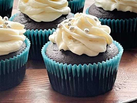 A close-up image of a chocolate miso cupcake with white frosting and silver sprinkles, on a wooden board.