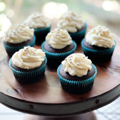 Chocolate miso cupcakes with white frosting topped with silver sprinkles, on a wooden board.