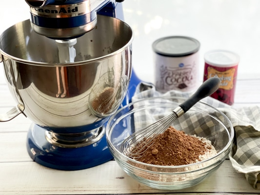 A clear mixing bowl filled with flour and cocoa powder and a whisk on top, and a blue Kitchen Aid mixer on the side, with boxed ingredients in the background.