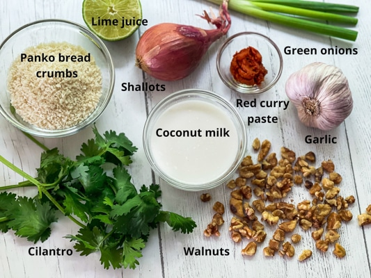 Ingredients on a white board for making walnut crusted halibut, including bread crumbs, coconut milk, walnuts, and red curry paste.