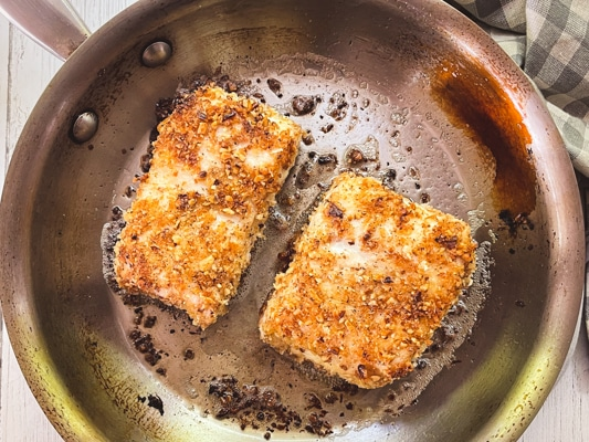 Two pieces of golden brown halibut fillets being seared in a stainless steel frying pan.