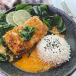 A beautiful piece of golden crusted halibut fillet in a black bowl with a vibrant red curry sauce at the bottom of the bowl, and white steamed rice and spinach on the side.