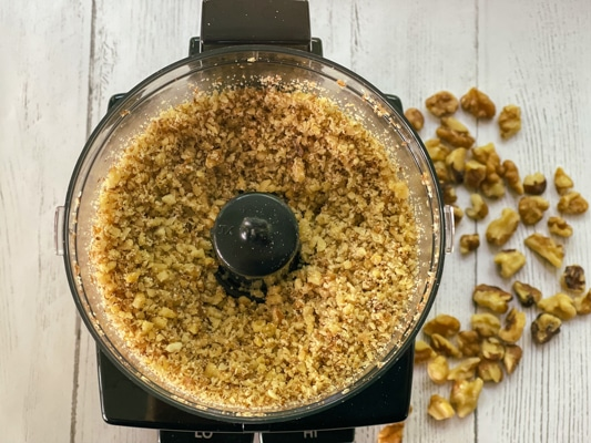 Chopped walnuts in a food processor with pieces of walnuts on a white board.