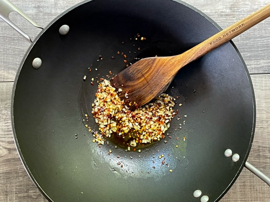 Garlic and red pepper flakes frying in a black wok with a wooden spatula inserted.