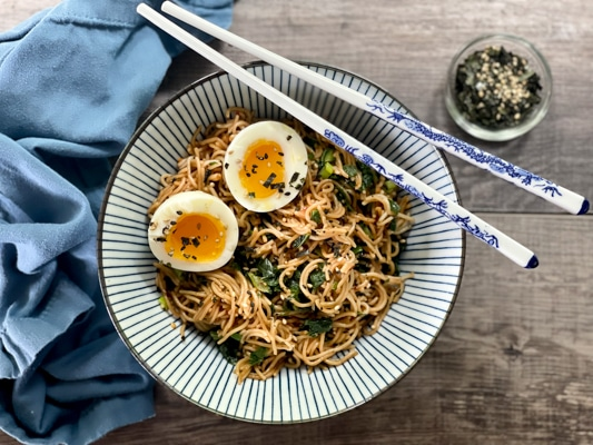 A striped bowl filled with ramen noodles topped with two runny eggs, with chopsticks laying on top of the bowl.