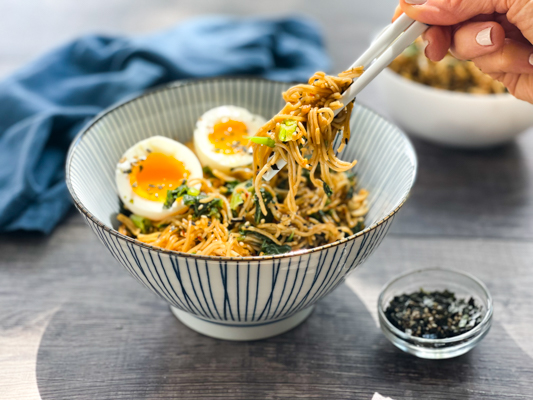 A striped bowl filled with ramen noodles topped with two runny eggs, and a woman's hand with chopsticks picking up some noodles.