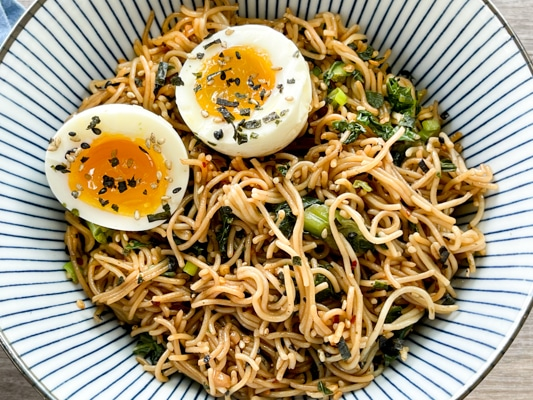 A striped bowl filled with ramen noodles topped with a runny egg.