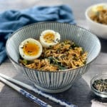 A striped bowl filled with ramen noodles topped with two runny eggs, with chopsticks laying on the side.