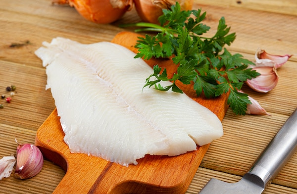 A piece of halibut fillet on a wooden cutting board with a knife, fresh herbs, and garlic cloves on the side.