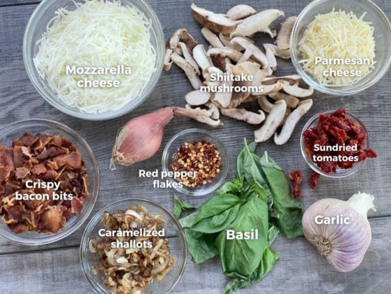 Ingredients on a board for making cauliflower pizza, including bacon bits, caramelized shallots, two cheeses, basil, shiitake mushrooms, sundried tomatoes, and basil.