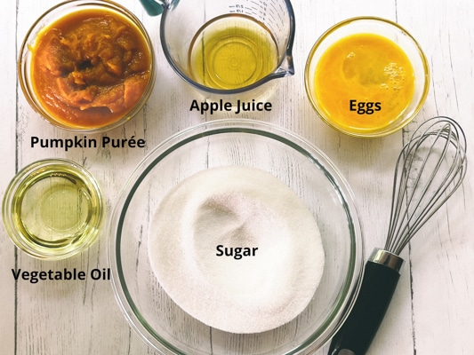 Ingredients for making pumpkin muffins on top of a white board with a whisk on the side.