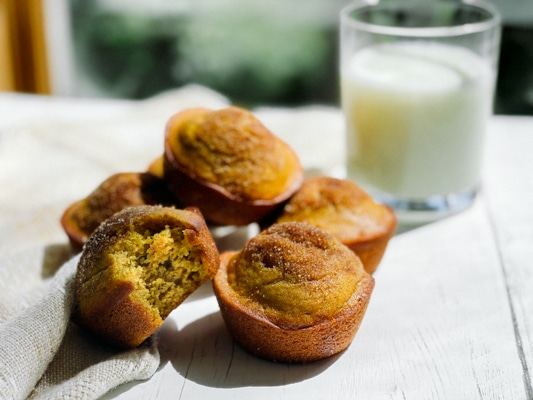 A stack of pumpkin muffins on a white board with a glass of milk in the background and a napkin on the side.