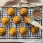 Freshly baked pumpkin muffins on a wire baking rack with a woman brushing the tops with butter.