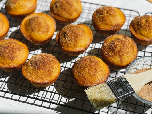 Freshly baked pumpkin muffins on a wire baking rack with a basting brush on the side.