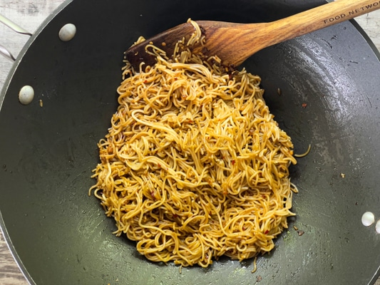 Ramen noodles frying in a large black wok, with a wooden spatula inserted inside.